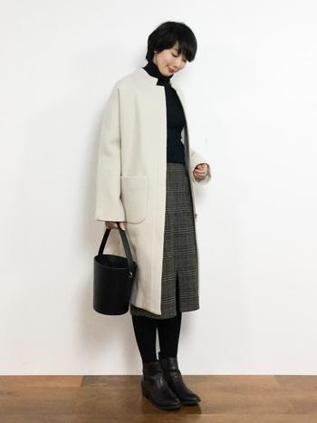 グレンチェックのひざ丈スカートは、清潔感のある白コートと好相性。モノトーンでシンプルにまとめたら、よそいきにもOKな上品な装いに。
