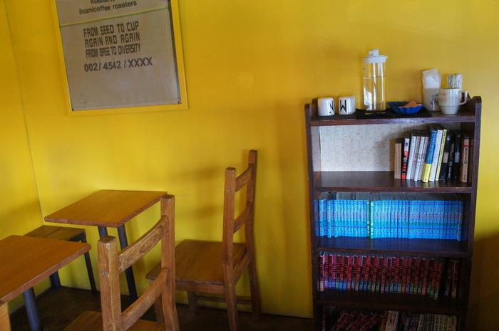 マヌ コーヒーは、福岡にて数点店舗がある人気のおしゃれカフェです。外壁は鮮やかな青、内装は落ち着いた黄色の壁が特徴的です。本棚には漫画が置かれていますが、全体的にアート感が強く、ゆっくりと過ごせる空間です。