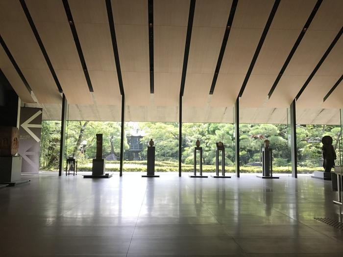 """""""庭と一体化した、環境と融合したミュージアム""""をコンセプトにした空間。広いガラスの壁面によって、庭の自然と古い東洋のアート作品が引き立て合い、時空を超えた世界への扉が開かれるよう。"""