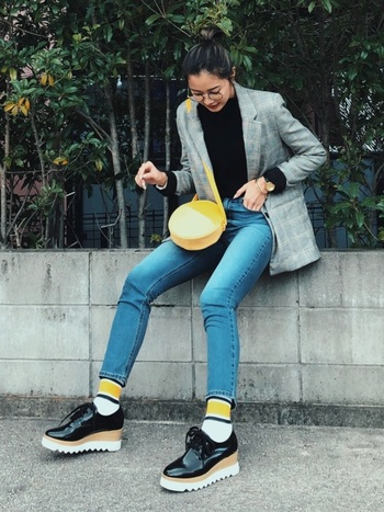 秋冬シーズンは靴下やバッグなど、小物でイエローを取り入れるのもおすすめです。鮮やかなイエローを差し色にすれば、いつものコーディネートが新鮮な印象になります。