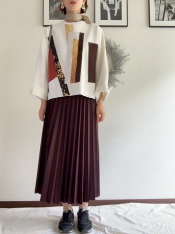 シックで女性らしいワインレッドのプリーツスカート。個性的なデザインニットも、柄に同系色があると統一感のある印象に。足元は、シンプルな黒スニーカーでカジュアルダウンしながらも、品よくまとめています。