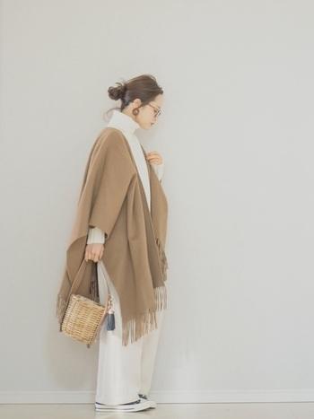 ホワイトのワントーンコーデにフリンジポンチョを羽織ったナチュラルコーデに大人っぽいバケツ型かごバッグの組み合わせ。女性らしく優しいスタイリングに心も温かくなります。