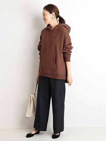 ブラウンのパーカーには、シックに黒いパンツと黒パンプスを合わせて。より女性らしく着こなすなら、ピアスやバッグもレディなアイテムを選びましょう。