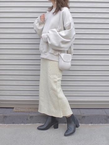一見グレーがかったホワイト系のスウェットに、ケーブルニットのタイトスカートを合わせて1トーンコーデに。足元はブラック系のショートブーツで印象を引き締めましょう。