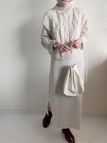 ワンピースに、ケーブル編みのニットベストを重ねて。 足元だけ黒で引き締めると、白のグラデーションが引き立ちます。 時計やアクセサリーで、より上品な印象に◎
