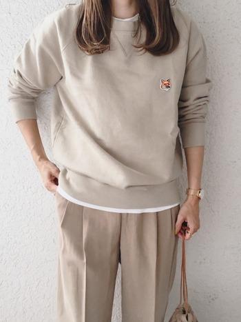 センタープレスのパンツに、同系色のスウェットを重ねて。優しいベージュを選ぶと、余裕のある大人の休日スタイルになります。