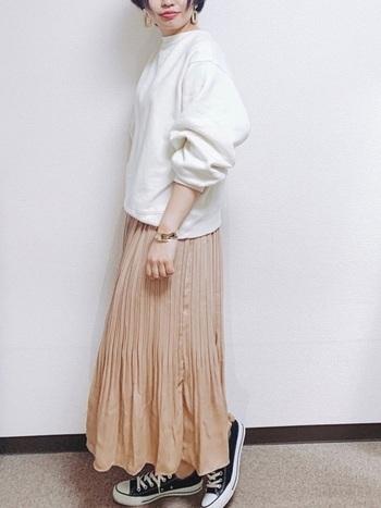 優しいベージュのスカートにはオフホワイトのスウェットを合わせて爽やかなカラーリングに。コーデの引き締め役には黒のスニーカーを合わせましょう。