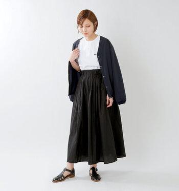 白のヘンリーネックシャツに、ダークネイビーのカーディガンとブラックのスカートを合わせたモノトーンコーデ。足元のサンダルをブーツに変えたり、タイツを合わせたりすることで、冬まで大活躍してくれるシンプルな着こなしです。