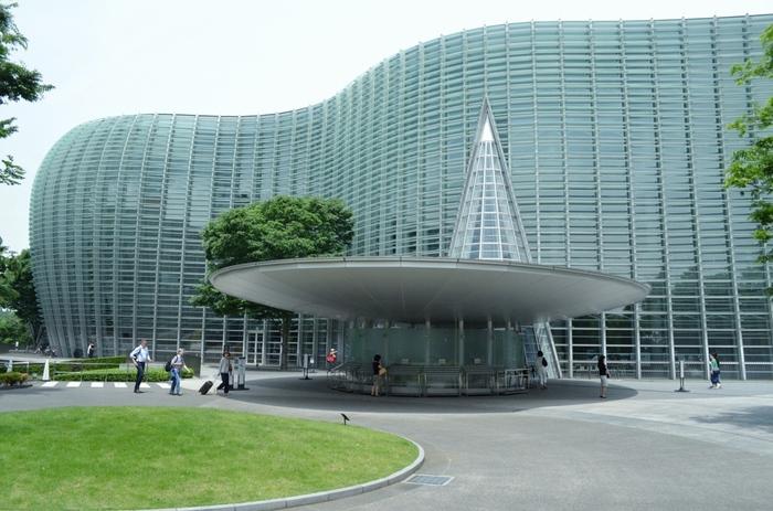 """「国立新美術館」は、地域の緑にとけこむような""""森の中の美術館""""をコンセプトに設計された国内最大級の展示スペースを誇る美術館。うねる波のようなガラスの曲線が美しい近代的な建物は、日本を代表する建築家の一人、黒川紀章氏の設計によるものです。"""