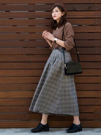 グレンチェックのフレアスカートを着用。合わせたバッグ、ベルト、シューズなどの小物を黒で統一して上質感アップ。