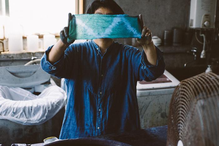 藍は酸化することによって発色するという特徴があるため、色を濃くするためには染め液に漬けては取り出し、空気に触れさせるという作業を何度も行う必要があります。こうした手間と時間のかかる作業をひとつひとつ繰り返すことによって、緑から美しい藍色へと変化していきます。