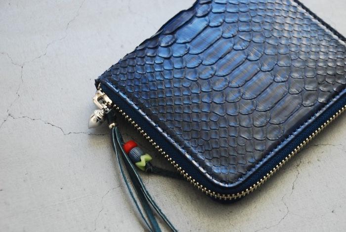 """こちらは素材とデザインにこだわった上質なアイテムを発信するブランド、「BRU NA BOINNE(ブルーナボイン)」の藍染めのウォレットです。素材に使用しているのは、美しいウロコ模様が特徴のダイヤモンドパイソン。そのダイヤモンドパイソンの革を脱色して模様を消し、徳島県の伝統技術""""阿波正藍(あわしょうあい)""""で藍染めにしてヌバック仕立てに仕上げた逸品です。持ち手部分の飾りには100年以上前のアンティークビーズを使用しており、その組み合わせは一点一点異なります。"""