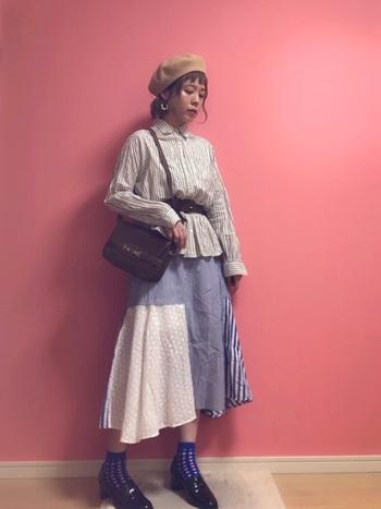 パッチワーク柄のような主張のあるスカートにも合わせやすいストライプシャツを使ったコーデ。  スカートにもストライプ柄が入っているため、統一感がプラスされています。  あえてウエストの高い場所でベルトをすることで、シャツもスカートと同じような裾感に演出できているのもポイント。  ソックスも、スカートのカラーリングに寄せたデザインでおしゃれですね。