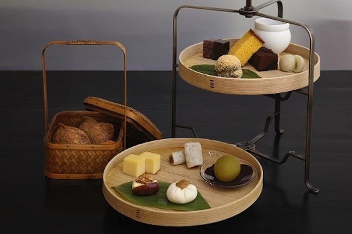 モダンな和菓子で人気の「HIGASHIYA(ヒガシヤ)」の銀座店では、少し変わった和のアフタヌーンティーを体験することができます。画像のアフタヌーンティー「茶間食(さまじき)」は、一の盆にはいなり寿司、二の盆には卵焼きや間食、三の盆には季節の和菓子が美しく盛り付けられています。