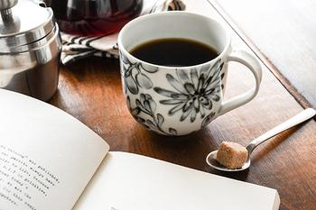 モノトーンで描かれた草花が水墨画のよう。華やかでありながらシックな雰囲気も漂うマグカップです。