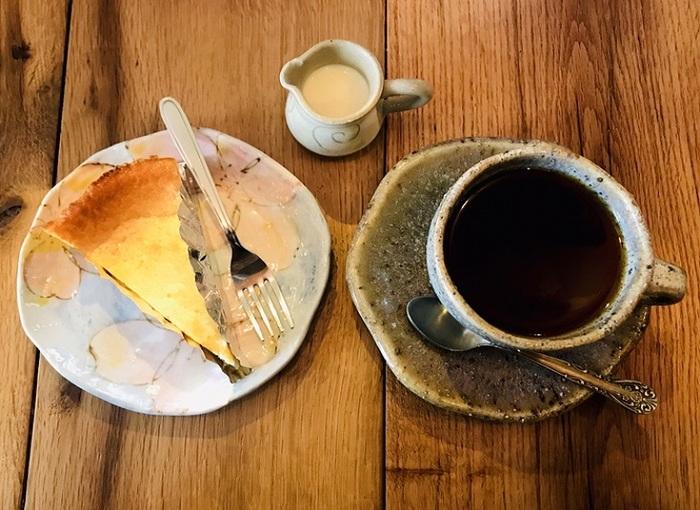 """チーズがふんだんに使われたベイクドチーズケーキはお店の""""顔""""。民芸風なカップがいい味わい。※自家焙煎コーヒー豆が購入できます。"""