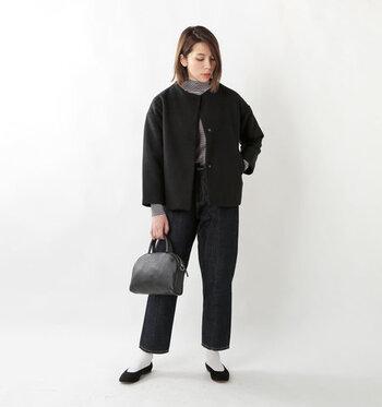 黒のショート丈ノーカラーコートに、ハイネックのボーダートップスとデニムパンツを合わせたコーディネートです。全体をダークトーンでまとめつつ、白靴下×黒パンプスの組み合わせで程よく見栄えするアクセントカラーをプラスしています。