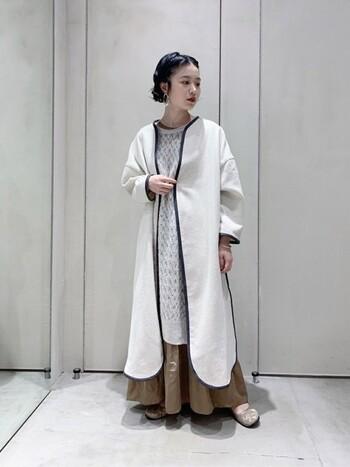 ワンピースにロングスカートをレイヤードし、さらに上からロング丈のノーカラーコートを羽織ったスタイリングです。丈の長さを少しずつ変えることで、数枚のアイテムを重ねてももたつきを感じさせないスタイリングが叶います。