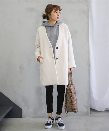 アイボリーのノーカラーコートに、グレーのパーカーとタイトなパンツを合わせた着こなし。足元は黒のスニーカーで、カジュアルさとフェミニンさを上手にミックスさせています。