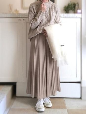 冬の定番ケーブルニットにプリーツスカートをあわせた、やさしい雰囲気のワントーンコーデ。落ちついた配色で季節感も出ています。白のスニーカーやストールがヌケ感をプラスして、明るい印象になっています。