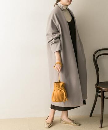 今年トレンドの巾着バッグ。様々な形のタイプが出ていて、女性らしいファッションに合わせれば、バッグがより引き立ちます。落ち着きあるイエローカラーの巾着バッグには、ライトグレーのエレガントなコートを合わせてワンポイントに。