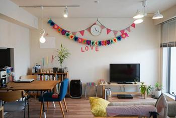 シンプルなお部屋のなかで、ガーランドがインテリアのアクセントになっています。カラフルなガーランドが、お部屋全体を明るい雰囲気にしています。2種類で飾り方を少し変えているところも、参考になりますね。