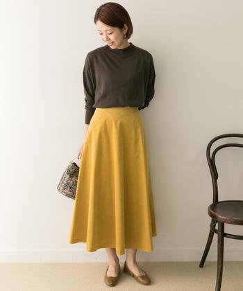 パッと目を引く明るめイエローのフレアスカートに、ブラウンのハイネックトップスを合わせたコーディネートです。全身が派手な印象にならないよう、スカート以外はブラウン系で統一して色数を抑えた着こなしに。寒い日は、足元はショートブーツなどに変えても◎。