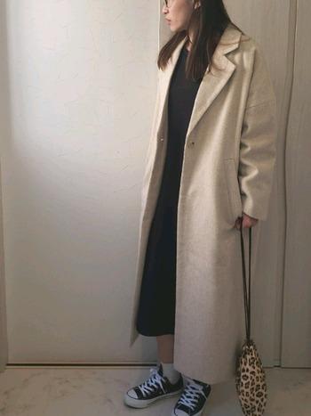 ベージュのチェスターコートは、足首上のマキシ丈。大人な印象なので、中にはワンピースとスニーカーで少女っぽさを加えて。小物で小気味いいアクセントをプラス。