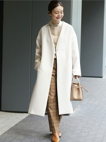 雪のようにピュアで綺麗なホワイトコートには、優しいベージュコーデを合わせて、モノトーン以外の楽しみ方をしましょう。キャメルのブーツで異素材をプラスするのもオシャレ。