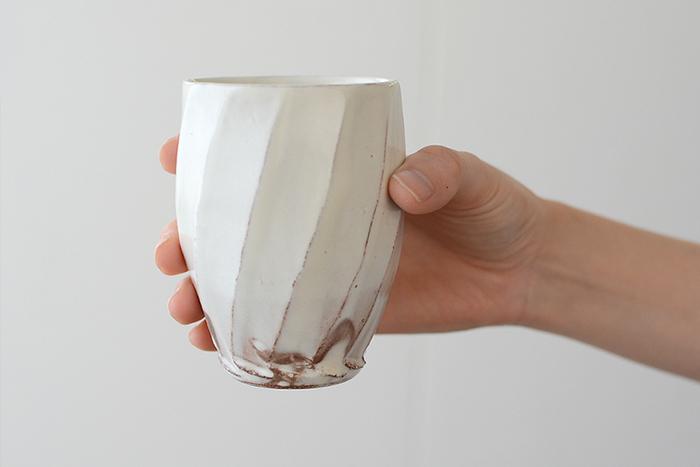 こちらは粉引の上品な白と、手彫りで仕上げた斜めのラインがおしゃれなフリーカップです。素朴な風合いのフリーカップは、ナチュラルな木の器やカトラリーとの相性も抜群です。先ほどの汲み出しに比べて高さがあるので、カップとしてだけではなく、木のスプーンやフォークを入れてカトラリーケースとしても使用できますよ。