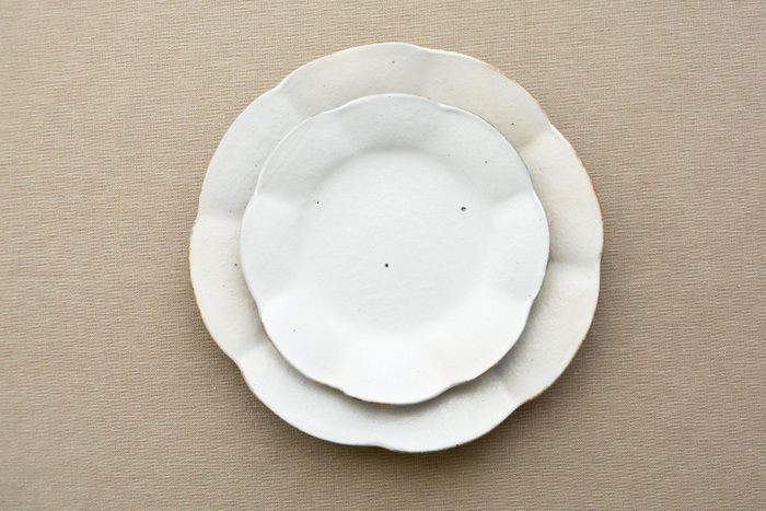こちらは花びらの形を模した可憐なデザインと、温かみのある素朴な風合いが特徴の輪花皿です。シンプルながらも確かな存在感を放ち、食卓をおしゃれな雰囲気に演出してくれます。こちらの写真は上が直径約16㎝、下が直径約21.5㎝の輪花皿です。どちらも日常使いしやすい程よい大きさで、和・洋様々な料理に活躍してくれます。
