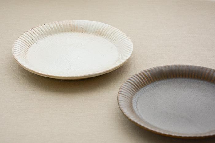 こちらはリムの部分に細かい線模様を施した、繊細かつ上品なデザインが特徴のラッフルプレート。白い粉引も茶色の錆釉も、どちらも土の素朴な素材感と優しい風合いが魅力的です。どんな料理も美味しそうに引き立てて、毎日の食卓を温かい雰囲気に演出してくれます。