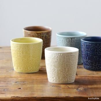 鳥や花のパターンが隙間なく描かれた、ナチュラルな雰囲気のマグです。デザイナーの伊藤利江さんが、自作のハンコを陶土に押して、このデザインを作り上げました。持ち手がないカップだからこそ、和洋問わずにティータイムに活躍してくれるアイテムです。