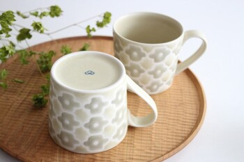 北欧の雰囲気を感じさせる、グレーフラワーが並んだデザインのマグカップ。でこぼことした表面の質感に、大人の遊び心が隠されています。一つ一つ丁寧に手描きされているため、それぞれのマグカップでも少しずつデザインに違いが表れるのも魅力的ですね。