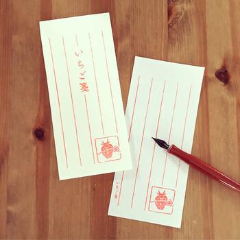 赤い罫線と、苺の果実と花をあしらったデザイン篆刻がかわいらしい一筆箋。ひとあし早い春の便りにいかがでしょうか?