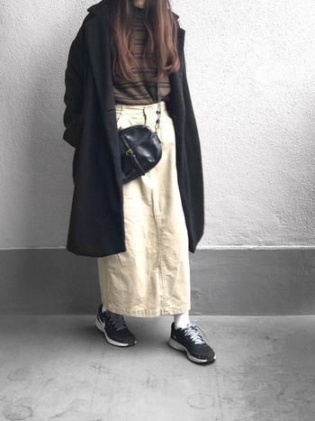 ブラックのチェスターコート。コートとのコントラストが効いたロングスカートに、ブラウンベースのボーダートップスを忍ばせて、統一感のあるシックなカジュアルコーデに。