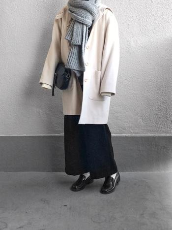 フードとボタンが印象的なコートは、モノトーンコーデがお似合い。ニットのグレーマフラーでコーデのポイントを作り、目線を上に上げることでよりお洒落でスマートなバランスになります。