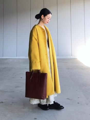 印象的なイエローのコートは、ドラマティックなワンピースを合わせてもちぐはぐしない実力の持ち主。大きなバッグやクラシカルな足元でらしさを出したコーデに。ヘアをスッキリまとめるのもポイント。