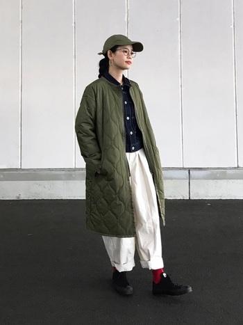 オーバーサイズのキルティングコートは、太めの白いパンツとキャップでボーイズコーデに。差し色はソックスの赤でさりげなく取り入れて。