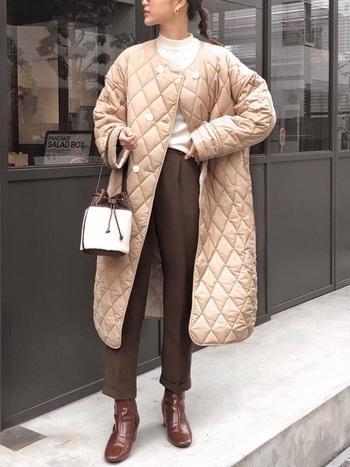 ベージュの上品なキルティングコートは、白とブラウンのコーデでグラデーションをイメージしたカラーリングで仕上げましょう。可愛らしいコロンとしたバッグがアクセント。