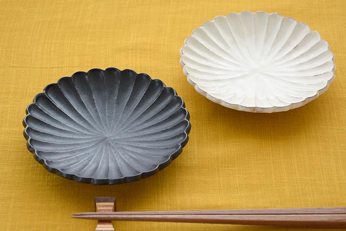 こちらは花びらを模した華やかなデザインが人気の輪花皿です。シックな黒釉と上品な粉引の白い輪花皿は、どちらも手仕事の温もりを感じる優しい風合いも印象的です。型を使わずに一枚一枚手彫りで仕上げているため、微妙な線の違いによって味わいある陰影と立体的な表情が生まれます。