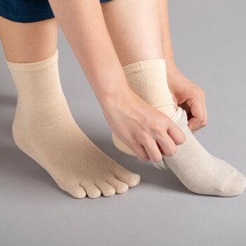 絹素材と綿素材の靴下を2枚重ねて着用する「冷えとり靴下」。2枚重ねで4枚分の暖かさを得られるよう、靴下そのものの内側を絹、外側は綿で織り上げています。
