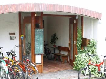 白を基調とした壁にウッドと緑の葉があたたかな雰囲気を出してくれます。カフェは2階へ上がったところにあります。