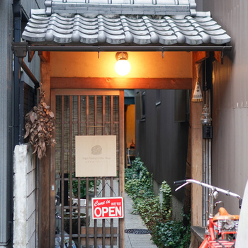 入り口はこちら。瓦屋根と引き戸が、和の趣があり素敵ですね。この門をくぐり、細い石畳を進んだ先にカフェの玄関口が待っています。