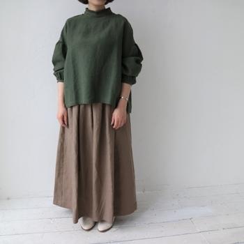 ブラウンのリネンスカートを着用。たっぷりと入ったギャザーと相まって温かみと柔らかさが演出され、夏とはまた異なる表情でリネンを着こなし。