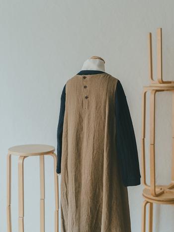 重ね着をする際に意識したいことがもうひとつ。それは、デザインポイントを隠してしまわないようにすることです。リネンウールのジャンパースカートは、斜めに配されたバックボタンがかわいいデザイン。なるべく見せたいので、インナーにハイネックのブラウスとキルティングのプルオーバーを重ねて、暖かさとおしゃれさを両立させています。