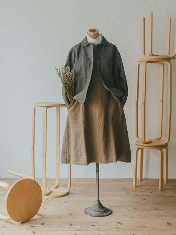 同じスタイリングにジャケットを羽織ったもの。ワンピースのスカート部がフレアになっているので、ボリューム感を生かすためにショート丈のアウターをチョイス。大きなパッチポケットもこれなら活用できます。一枚のワンピースが、アウターを着たときと脱いだときでガラッと違う見え方をして、おしゃれの楽しみが広がりそうです。  綿ウールスタンドカラーブラウス ¥16,500 アーミーストライプキルトプルオーバー ¥12,100 リネンウールポケットジャンスカ ¥17,600 リネンウールツイルジャケット ¥22,000/すべてYARRA
