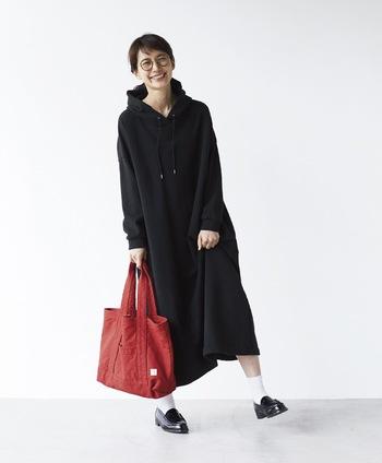 シンプルなトートバッグも赤にするだけで、ブラックコーデを印象的に。ゆったりとしたロングパーカーワンピースとバッグの大きさのバランスも上手く取れています。
