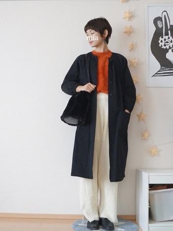 秋らしいオレンジ色のフェザーニットをインナーに。白のワイドパンツにボトムスインすることで、素材の近いファーバッグとブラックコートの組み合わせにメリハリがでて、大人の余裕を感じさせます。