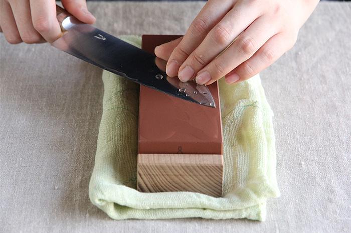 砥石はしっかりと水に浸したものを使います。濡らした布巾の上に乗せて固定し、包丁と砥石の間に10円玉3枚を挟むくらいの角度であてて研いでいきましょう。左手は指を3本ほど刃の上に添えて、優しく刃先を前後に動かします。